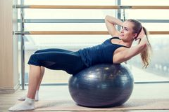 Young girl working out at the gym with a ball Royalty Free Stock Photo