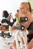 Young girl working out on weight machine Royalty Free Stock Images