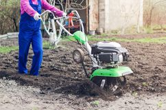 Young girl working in a spring garden with a cultivator.  stock photos