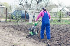 Young girl working in a spring garden with a cultivator.  stock image