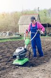 Young girl working in a spring garden with a cultivator.  stock photo