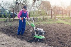Young girl working in a spring garden with a cultivator.  stock images