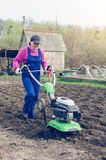 Young girl working in a spring garden with a cultivator.  royalty free stock photos