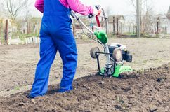 Young girl working in a spring garden with a cultivator.  royalty free stock image