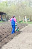 Young girl working in a spring garden with a cultivator.  royalty free stock images