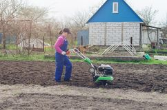 Young girl working in a spring garden with a cultivator.  stock photography