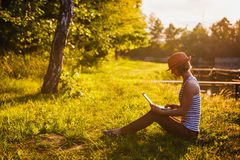 Young girl working/studing in the park stock photography