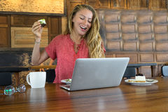 The young girl works at the computer and cake, food at the computer, a bad habit eats. Stock Photos