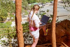 A young girl works with a laptop on the mountain overlooking the rainforest and the beach. Work and travel royalty free stock photo