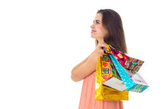Young girl is worth turning sideways and keeps bright colored shoulder bags isolated on white background Stock Photography
