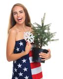 Young girl wrapped in an American flag isolated on white background with a Christmas tree and a snowflake in her hands. Young girl wrapped in an American flag Stock Images