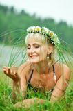A young girl in a wreath of chamomiles lies on a green meadow. Dreamy beautiful face stock image