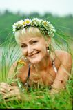 A young girl in a wreath of chamomiles lies on a green meadow. Wide, sincere smile stock photos