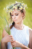 Young girl with wreath on golden wheat field Stock Images