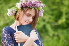 A young girl in a wreath of lilac with a book in hand Stock Photos