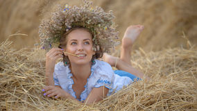 Young girl in a wreath resting in straw haystack