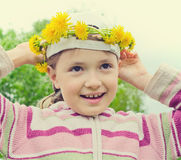 The young girl with a wreath from yellow flowers on the head Royalty Free Stock Photo