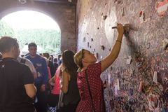 Young girl write a letter to Juliet on the wall in the passage t Royalty Free Stock Image