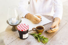 Young girl writes in a notebook with cell phone and cup of coffe Royalty Free Stock Images
