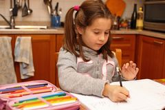 Young girl writes with pencil her homework in the kitchen Royalty Free Stock Images