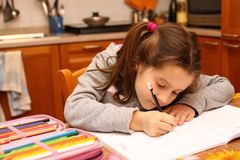 Young girl writes with pencil on the school book Stock Photos