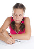 Young girl writes to writing-books Stock Photography