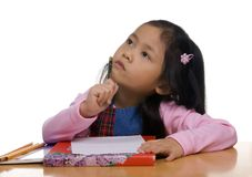 Young Girl writing 2. A young asian girl is thinking about what to write next Royalty Free Stock Photos
