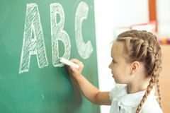 Young girl writing ABC on green chalkboard.  stock photos
