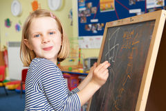 Young Girl Writing On Blackboard In School Classroom Royalty Free Stock Image