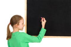 Young Girl Writing On A Blackboard. Smiling girl in green blouse holding white chalk writing on a blackboard. Head and shoulders studio shot isolated on white Stock Images