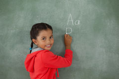 Young girl writing on chalk board. Portrait of young girl writing on chalk board royalty free stock photography