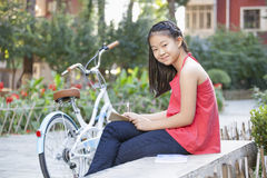 Young Girl Writing in a Courtyard with Her Bike Stock Photography