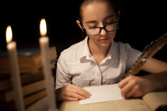 Young girl writing with feather Stock Photo