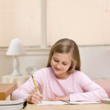 Young girl writing homework in notebook Stock Photography