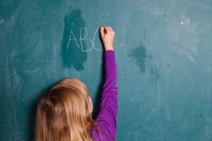 Young girl writing letters on chalkboard Stock Photo