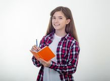 Young girl writing in notebook using pencil and smiling. Student, on white royalty free stock image