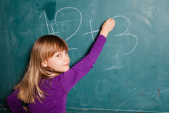 Young girl writing numbers on chalkboard Royalty Free Stock Image