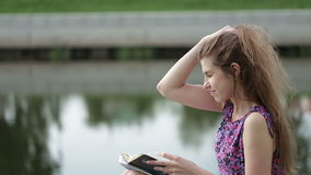 Young girl writing by the Riverside. Young woman sitting on a park and having an idea stock footage