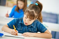 Young girl writing at school Stock Photos