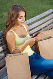 Young girl writing sms about her purchases Royalty Free Stock Photo