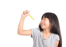 Young girl writing something with yellow pencil. Royalty Free Stock Image