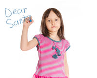 Young girl writing to Santa on imaginary board royalty free stock photos