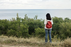Young girl (brunette) and jeans with a red backpack looking out Stock Images