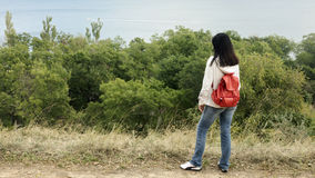 Young girl (brunette) and jeans with a red backpack looking out Royalty Free Stock Images