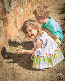 A young girl of 3 years and a boy of 5 years rest in a rock garden. Royalty Free Stock Image