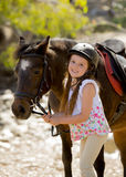 Young girl 7 or 8 years old holding bridle of little pony horse smiling happy wearing safety jockey helmet in summer holiday Stock Image