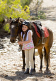 Young girl 7 or 8 years old holding bridle of little pony horse smiling happy wearing safety jockey helmet in summer holiday Royalty Free Stock Image