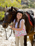 Young girl 7 or 8 years old holding bridle of little pony horse smiling happy wearing safety jockey helmet in summer holiday Stock Photography