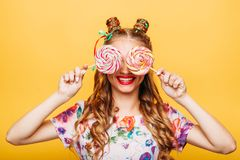 Young girl on the yellow background holding sweets Royalty Free Stock Photos