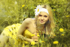 Young girl in yellow dress in field with camomiles. Stock Photography